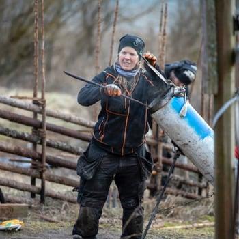 Gärdsgårdsbyggare Marie hämtar en ångkokad vidja för att binda gärdsgårsstören
